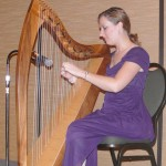 Executive assistant Laura Welker entertains on the Celtic harp during the silent auction.